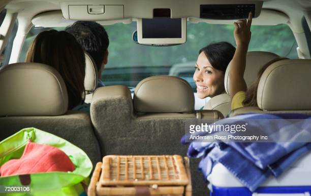 Family in car with cooler and picnic basket