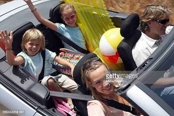 Family in convertible car, children (9-11) waving, smiling