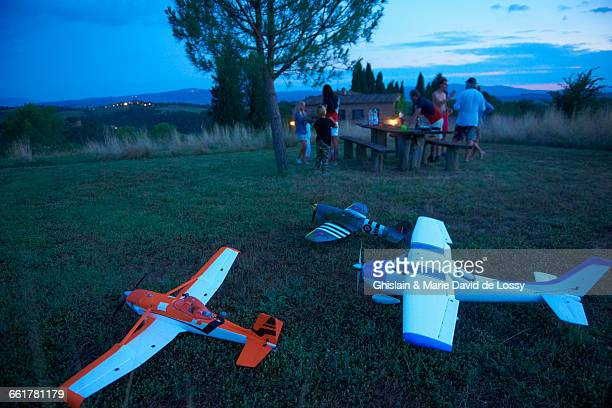 Family in field at dusk, remote control planes in foreground
