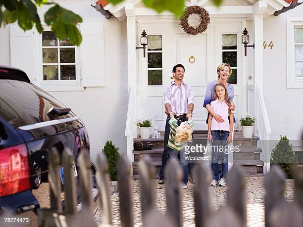 Parents with children (8-11) in front of house, smiling