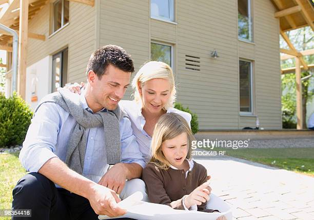 Family in front of residential home looking at blueprint