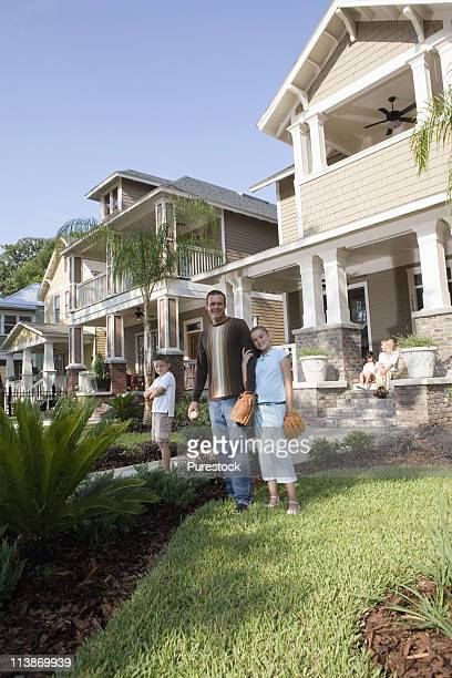 Family in front yard of house