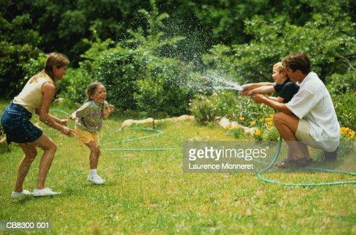 Family in garden, father and son (5-7) spraying garden hose