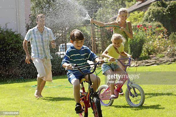 Family in garden with hosepipe, children on bikes