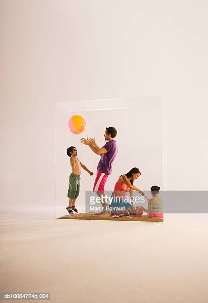 Family in glass cabinet, father and son playing with beach ball