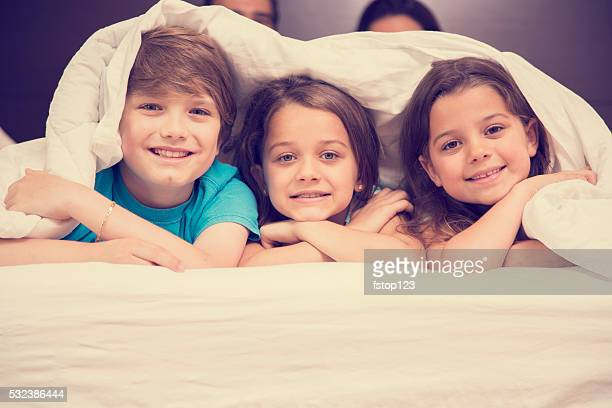 Family in hotel bedroom. Happy children on bed. Vacation, tourism.