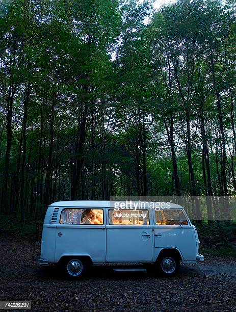 'Family in illuminated van in forest, side view, evening'