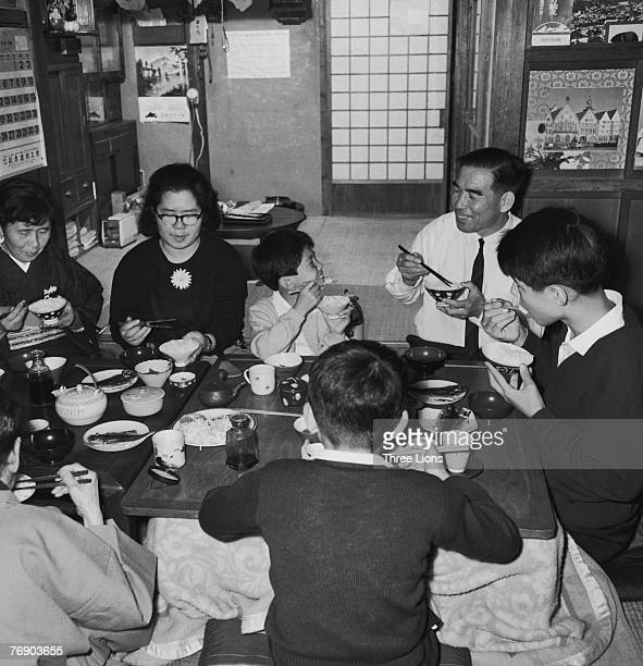 A family in Japan sit down to a meal together circa 1965