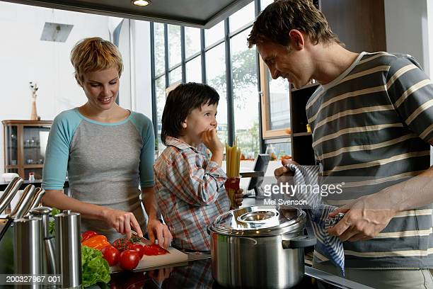 Family in kitchen cooking, father smiling at son (5-7)