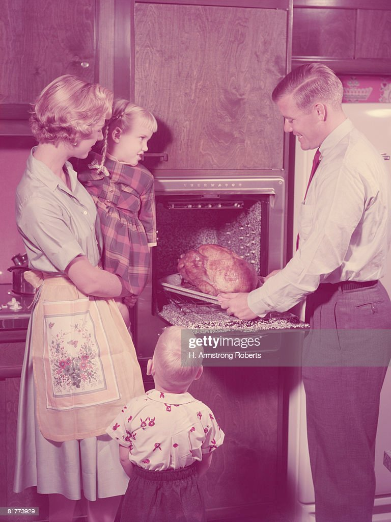 Family in kitchen, father taking roast turkey out of oven, mother and children looking on. (Photo by H. Armstrong Roberts/Retrofile/Getty Images) : Stock Photo