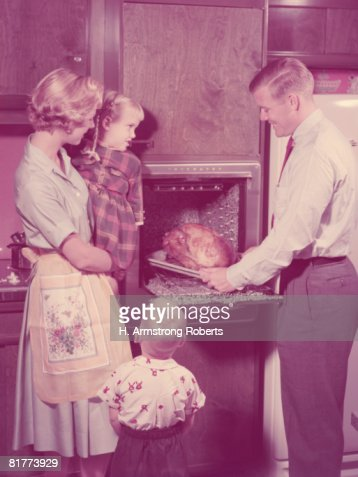 Family in kitchen, father taking roast turkey out of oven, mother and children looking on. (Photo by H. Armstrong Roberts/Retrofile/Getty Images) : Foto de stock
