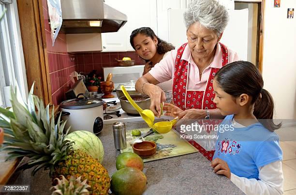 Familia en cocina, abuela ayudar a jóvenes granddaughter (6