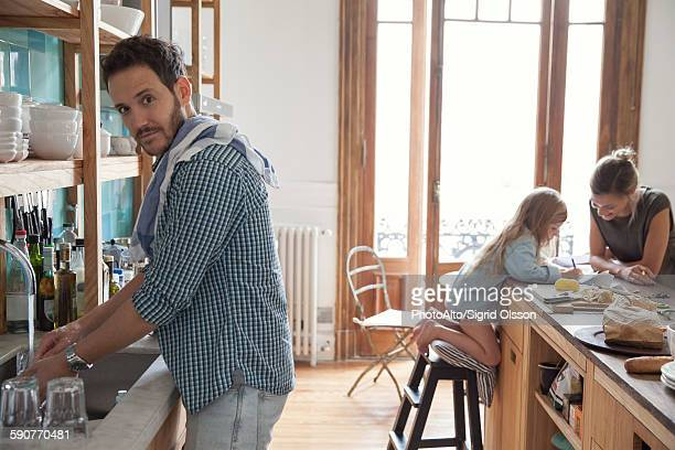 Family in kitchen, man doing dishes in foreground