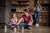 Cute little girl and her dad are using wooden spoons and smiling while playing drums with dishes in kitchen, mom is cooking