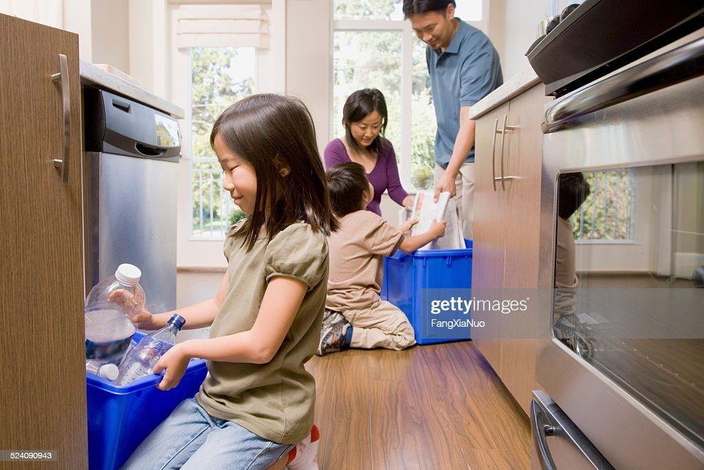 Family in Kitchen Recycling Paper and Plastic : Stock Photo