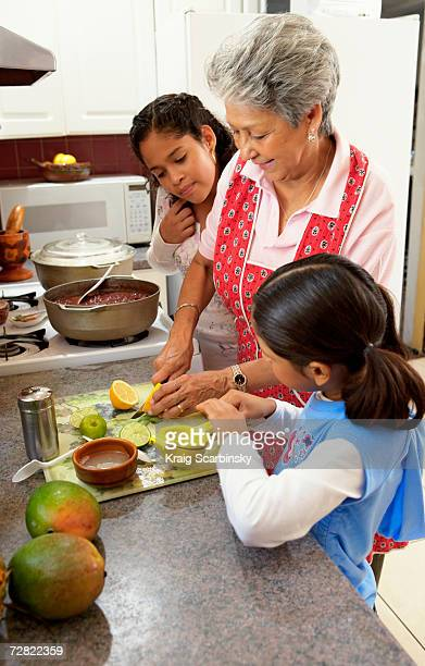 Family in kitchen, with granddaughters (6-12) watching grandmother slice citrus fruit