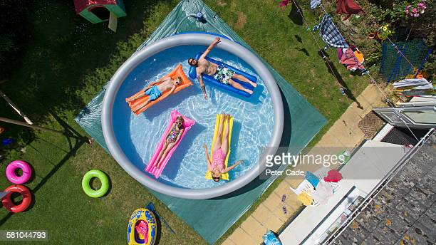 Family in large padding pool in garden