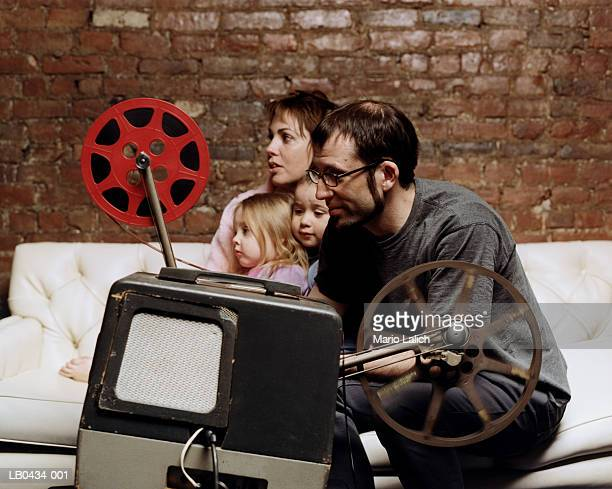 Family in living room, father operating film projector, profile