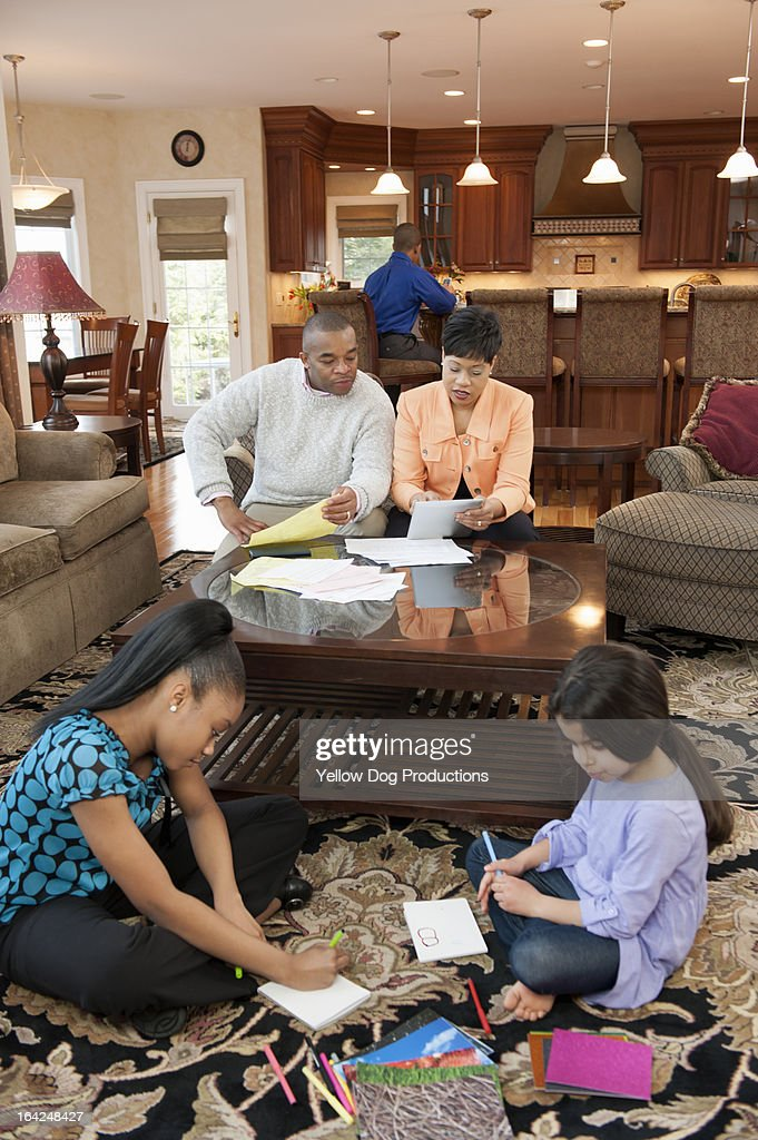 Family in living room, parents paying bills : Stock Photo