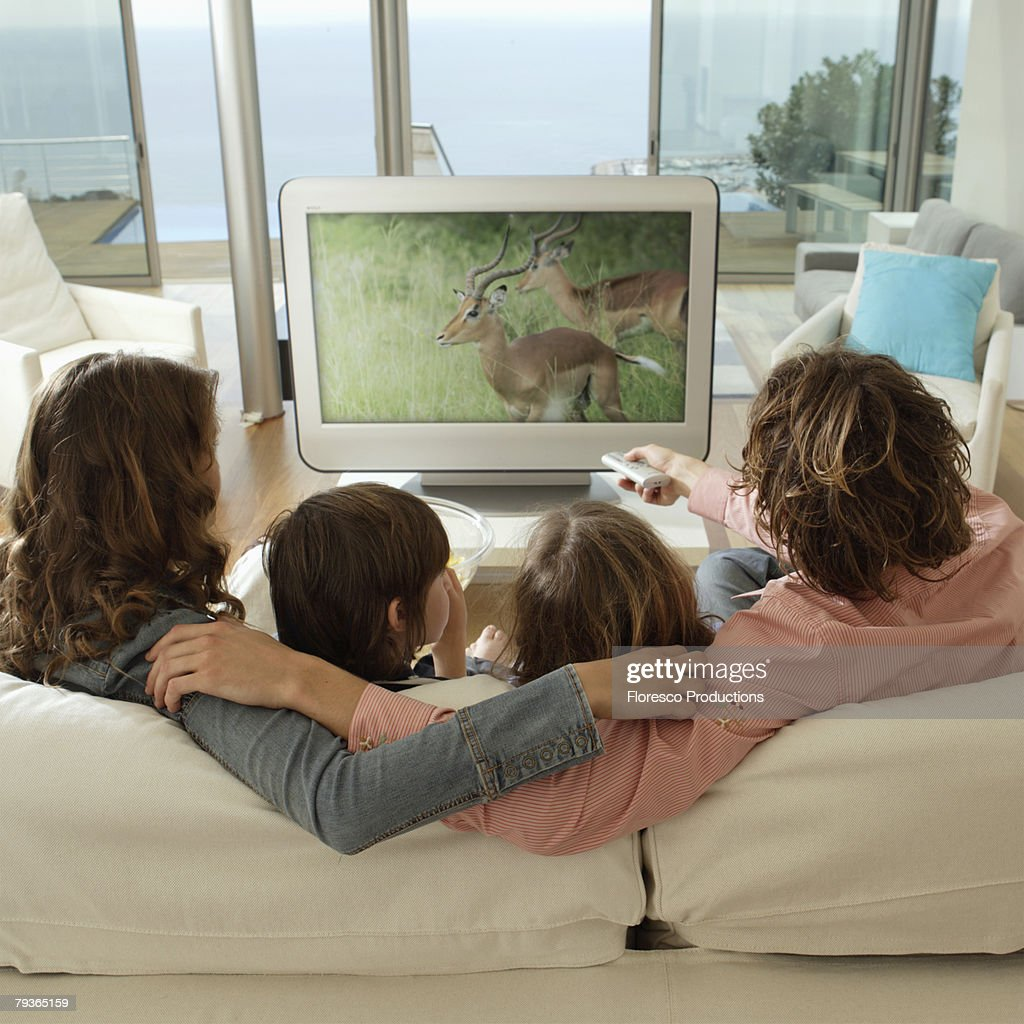 Family in living room watching television : Stock Photo