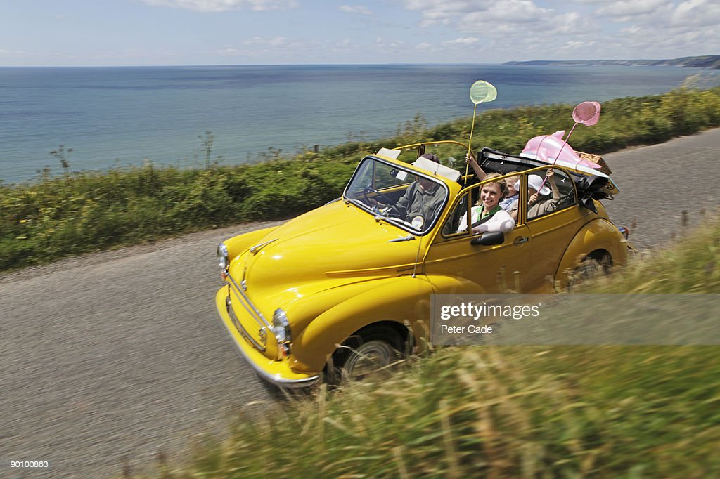 family in open top car on coastal road : Stock Photo