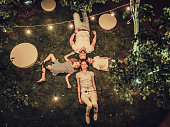 Top view of happy family is spending time together in park in the evening with garland of light bulbs. Parents with children are having fun and enjoying being together. Mom, dad, son and daughter outd