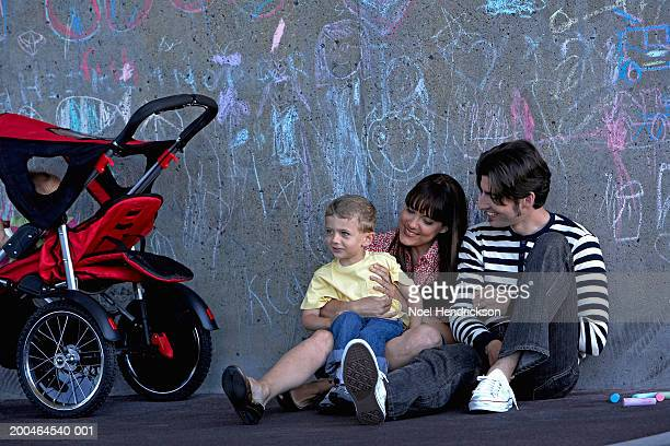Family in playground, sitting against wall covered in chalk drawings