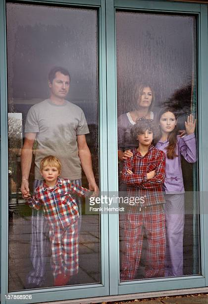 Family in pyjamas' looking out rainy window