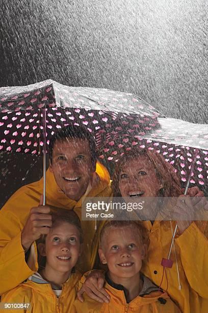 family in rain under umbrellas