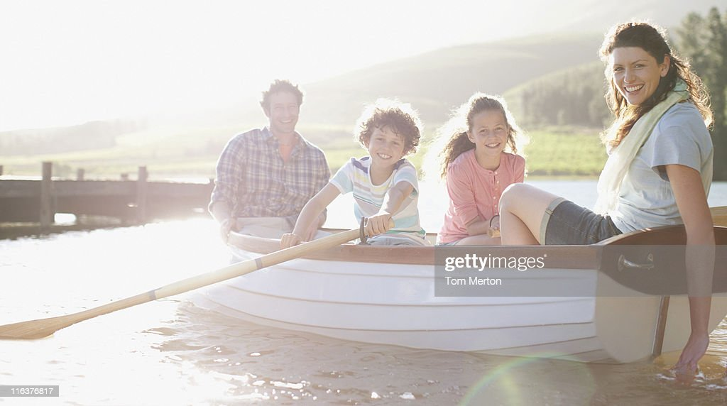 Family in rowboat on lake : Stock Photo