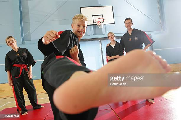 Family in sports hall doing tae kwon do