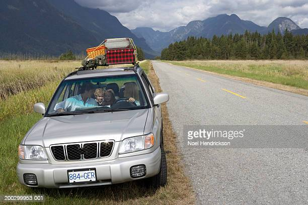 Family in sports utility vehicle parked on grass verge beside rural road