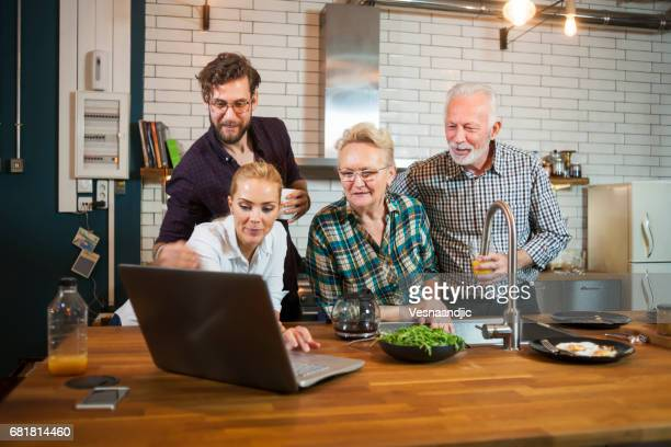 Family in the kitchen using laptop