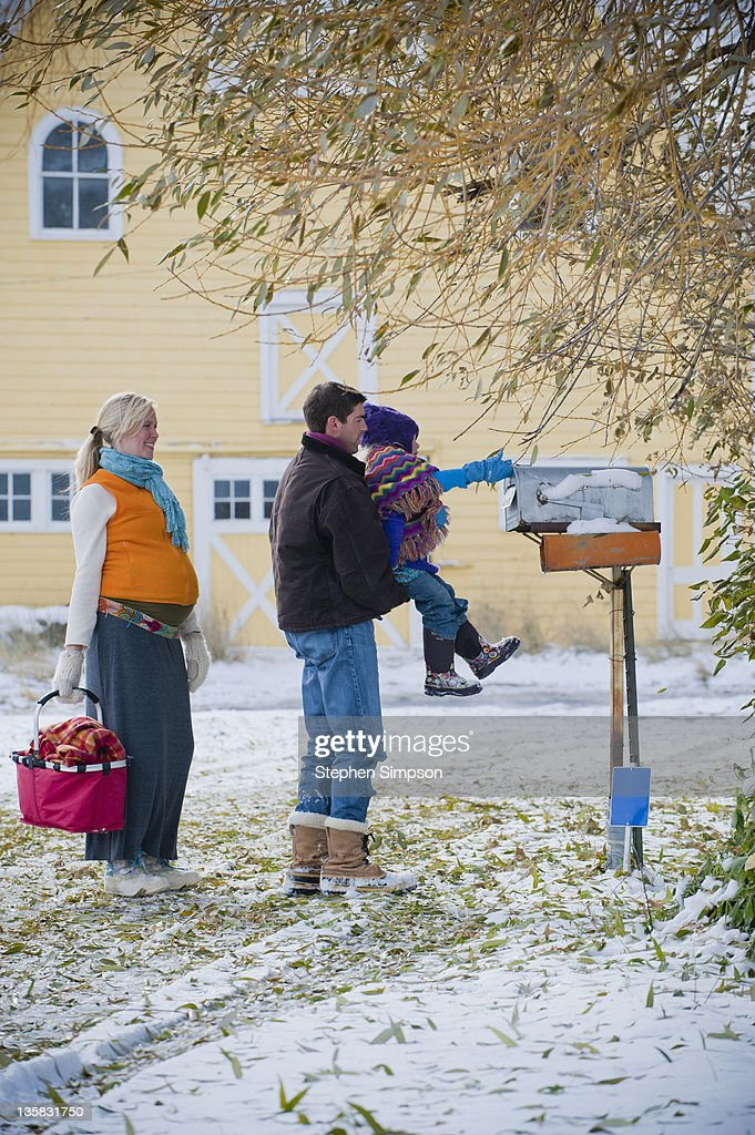 family in Winter checking the mailbox : Stock Photo