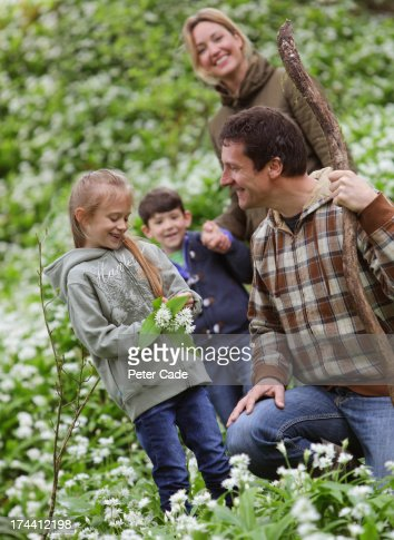 Family in woods picking flowers