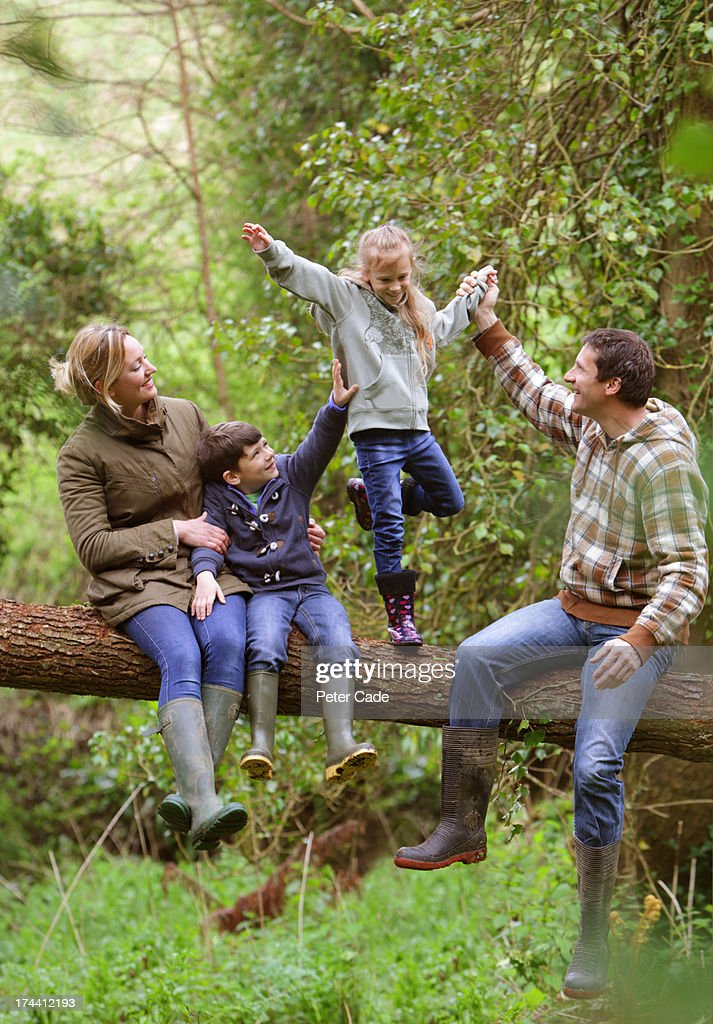 Family in woods sat on fallen tree : Stock Photo