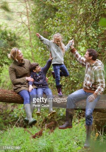 Family in woods sat on fallen tree