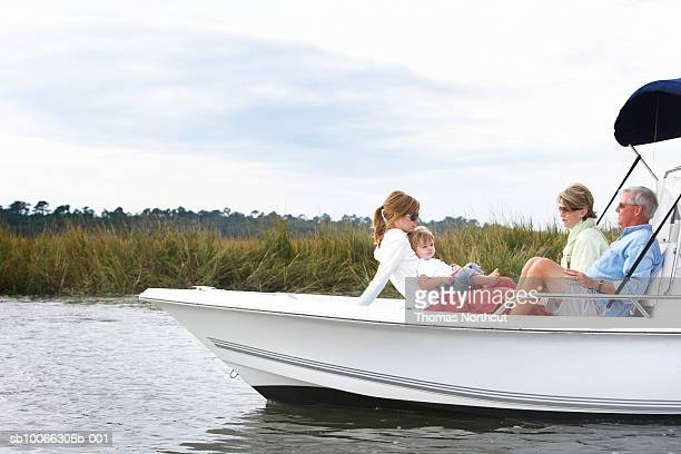 Family including boy (15-18 months) relaxing on boat
