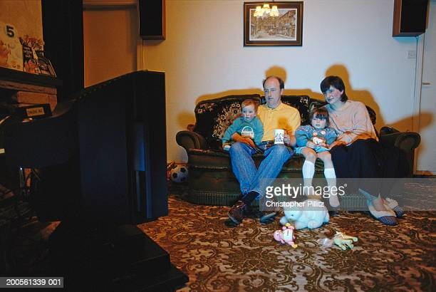 Family including children (2-4) sitting on sofa watching TV, night