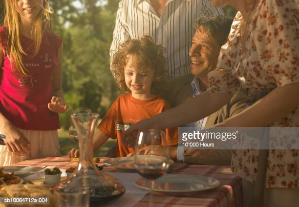 Family including two children (5-11) sitting at dining table in garden, smiling