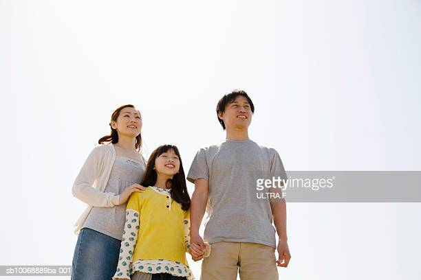 Family including young girl standing against clear white sky
