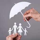 Hand holding an umbrella protecting a family