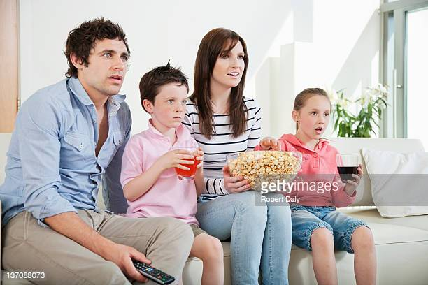 Family intently watching movie on sofa