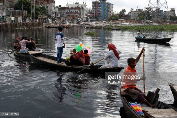 A family is crossing a polluted river near Dhaka