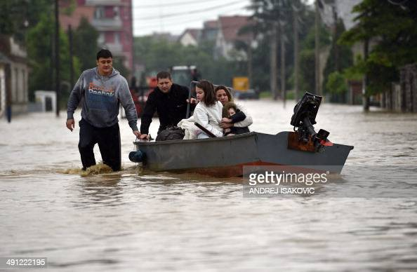 A family is evacuated by boat in the flooded town of Obrenovac 40 kilometers west of Belgrade on May 16 2014 Three people have drowned in Serbia and...