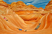A man with his two kids is lying in the beautiful Wave in Coyote Buttes, Arizona