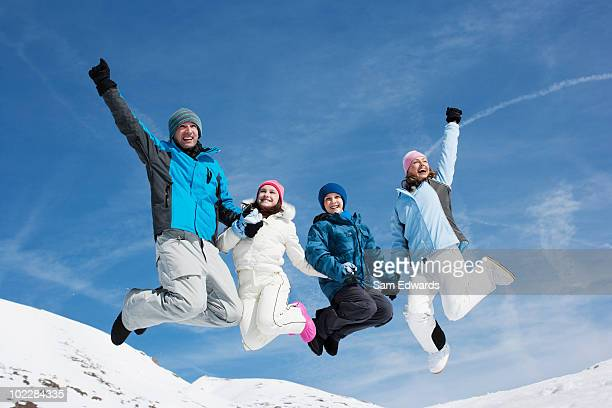 Family jumping in mid-air in snow