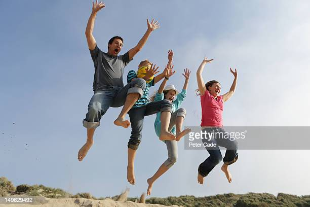 family jumping off sand dune
