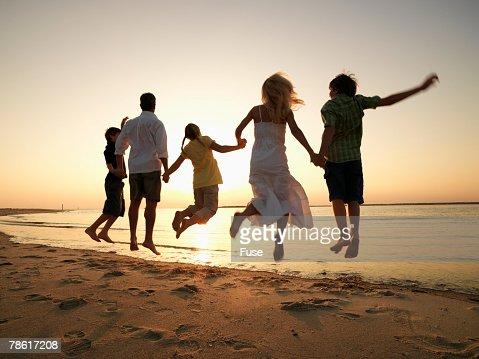 Family Jumping on Beach : Stock Photo