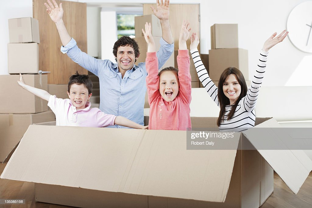 Family jumping out of moving box in new home : Stock Photo